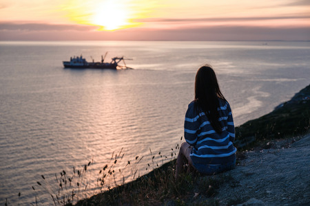 Unrecognizable woman in striped sweater admires the sunset on mountain with seascape view Back view. Stock Photo