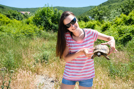 Woman brunette in sunglasses and striped t-shirt keeping turtle in her hands in the forest.