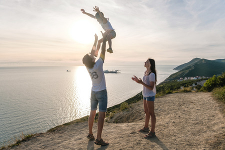Dad throws his son in the air, and mom looks at them on the mountain with seascape. Family trip. Zdjęcie Seryjne