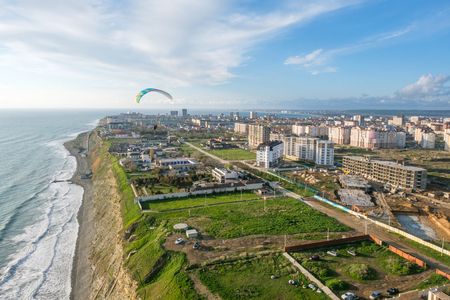 Flying tandem paragliders over the city on a Sunny day 스톡 콘텐츠