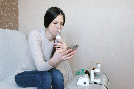 Use nebulizer and inhaler for the treatment. Young woman inhaling through inhaler mask and looking at phone. Side view.