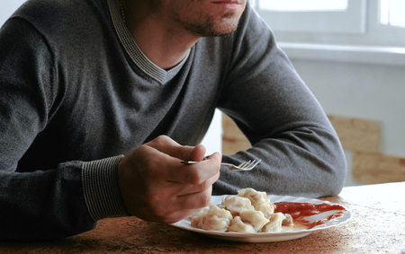 Unrecognizable man eats dumplings with a fork, putting them into tomato sauce in the kitchen. Stock Photo