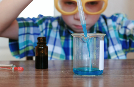 Experiments on chemistry at home. Boy pours blue liquid from a jar into a beaker with a pipette.