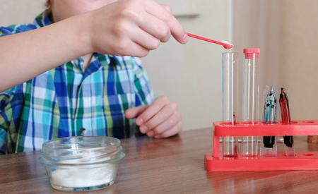 Experiments on chemistry at home. Boy conducts a chemical reaction in a test tube. Foto de archivo