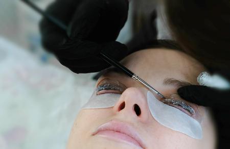 Beauty treatment. Beautician put a solution on curler eyelash curler with brush. lash lamination. Foto de archivo
