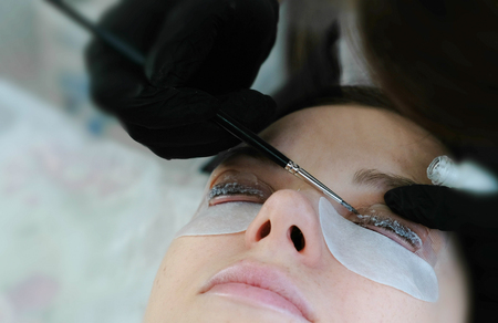 Beauty treatment. Beautician put a solution on curler eyelash curler with brush. lash lamination. Archivio Fotografico