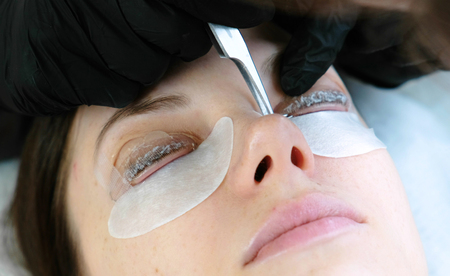Beauty treatment. Cosmetologist removes the solution from the lashes with tweezers. lash lamination. Closeup face.