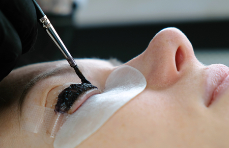 Beauty treatment. Cosmetologist puts black paint on the lashes. laminating eyelashes. Closeup face side view.