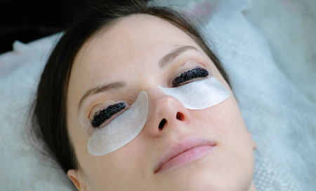 Beauty treatment. Closeup womans face with paint on eyelashes. laminating eyelashes. Top view.