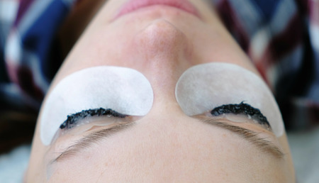 Beauty treatment. Closeup eyes in womans face with paint on eyelashes. laminating eyelashes.