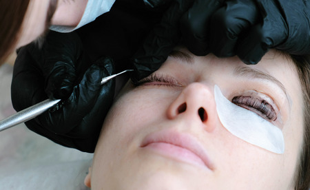Beautician removes paint from the eyes of the client with brush. lash lamination.