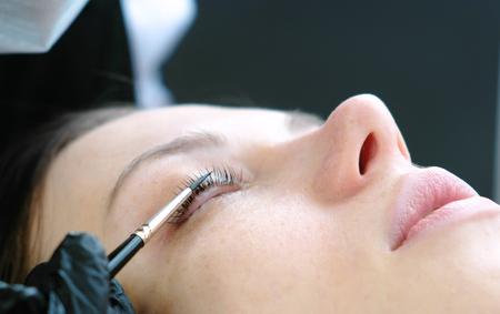 Cosmetologist rubs the clients eyelash with brush. lash lamination. Closeup eyes.