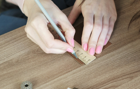 Seamstress measures segments on leather fabric with pencil and ruler, womans hands close-up. Imagens