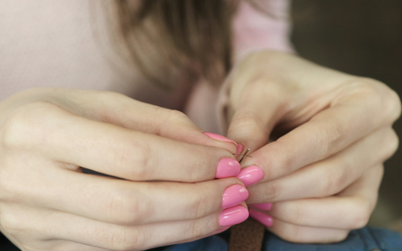 Close-up hands of a young tailor who puts thread in the needle. Stock Photo