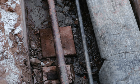 Closeup crash, burst pipes and leaking water under the earth. Excavated pipes in the winter.