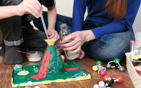 Chemical experiment. Close-up of the boys hands poured water from the bottle into the funnel of the volcano using a pipette.