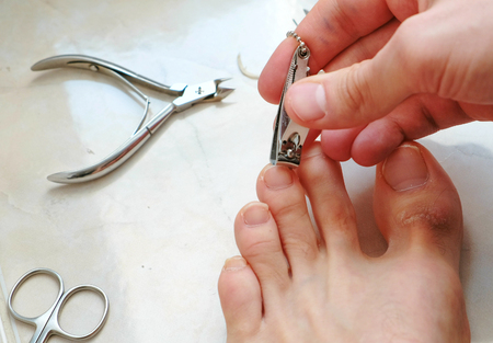 Man cutting toenails with clipper. Male cut toenails on foot. Foot and toes close-up. Top view.
