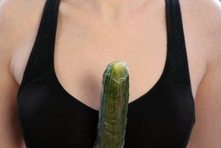 Closeup womans hands with dress the condom on cucumber.
