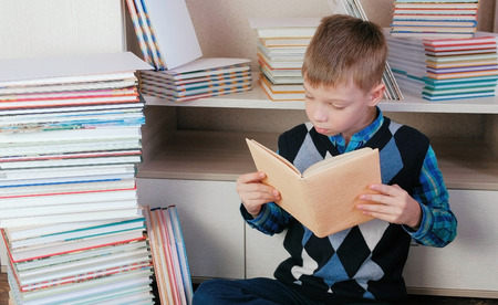 Seven-year-old boy attentively reads the book sitting among books.