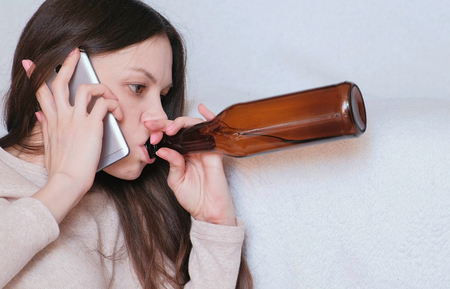 Tough conversation to women on the phone. Young beautiful woman drinks beer. Stock fotó