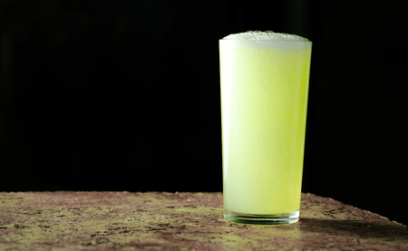 Full glass of a carbonated soda drink, yellow in color on a black background. Stok Fotoğraf