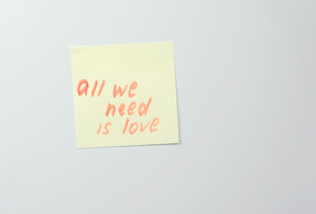 Note on yellow sticker paper sheets with motivation words all we need is love. Stok Fotoğraf