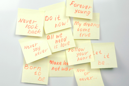 Yellow sticker paper sheets with motivation phrases on a white board. Stok Fotoğraf