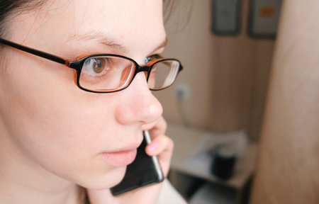 Woman in glasses is speaking mobile phone and looking ahead. Face closeup. Stock Photo