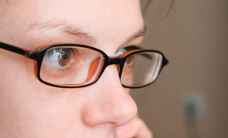 Woman in glasses is speaking mobile phone and looking ahead. Eyes closeup. Stock Photo