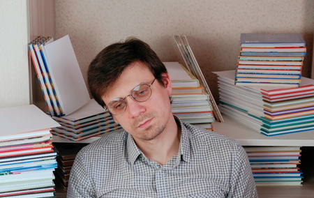 Young tired brunet man sitting among the books. 스톡 콘텐츠 - 102631237