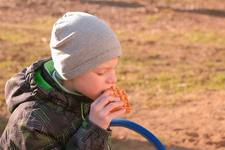 Boy eats waffles sitting on the bench in park. Stock Photo