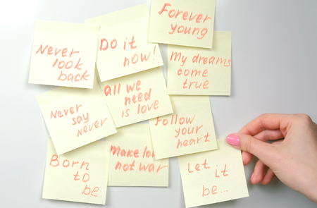 Closeup womans hands stick yellow sticker paper sheets with motivation phrases on a white board