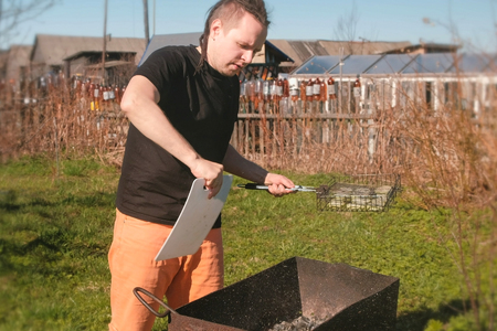 Young man inflates the coals in the grill brazier with a cutting Board.