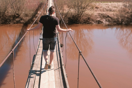 Young man is walking on a suspended wooden bridge over the river. Back view.