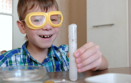 Experiments on chemistry at home. Smiling boy is looking at chemical reaction with the release of gas in the test tube in his hands.