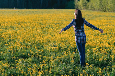Woman brunette walks on the field of yellow flowers. Stretches and breathes deeply. Banco de Imagens