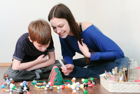 Mom and son looking at chemical reaction with gas emission. Experience with plasticine volcano at home. Stock Photo