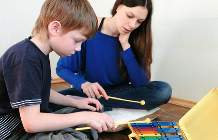 Playing music instrument. Boy repeats for the teacher playing the notes on the xylophone. Banque d'images