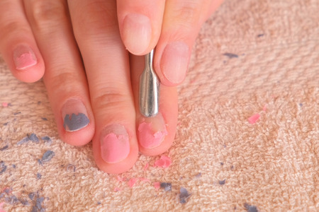 Woman removes shellac from nail with pusher. Close-up hand.