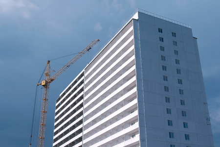 Construction of a multi-storey building. House and construction crane on sky background. Stok Fotoğraf