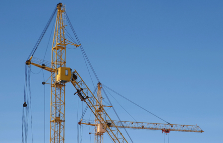 Two construction cranes against the sky background.