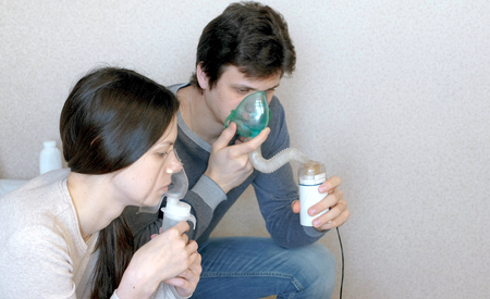 Use nebulizer and inhaler for the treatment. Man and woman inhaling through inhaler mask. Closeup side view.