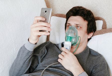 Use nebulizer and inhaler for the treatment. Young man inhaling through inhaler mask lying on the couch and chatting in mobile phone. Closeup front view.