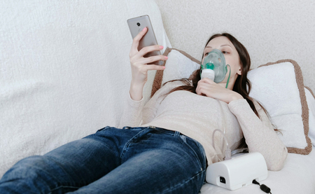 Use nebulizer and inhaler for the treatment. Young woman inhaling through inhaler mask lying on the couch and chatting in mobile phone. Front view.