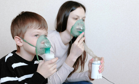 Use nebulizer and inhaler for the treatment. Woman and boy inhaling through inhaler mask. Side view.