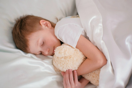 Seven-year-old boy falling asleep hugging toy bear. Stock Photo