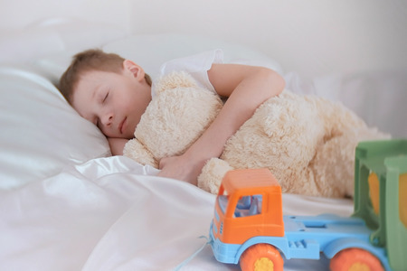 Seven-year-old boy sleeping with his toys bear and plastic car. Stock Photo