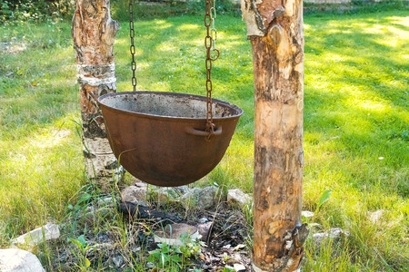 Cauldron, pot for cooking hanging on chains over the fire.