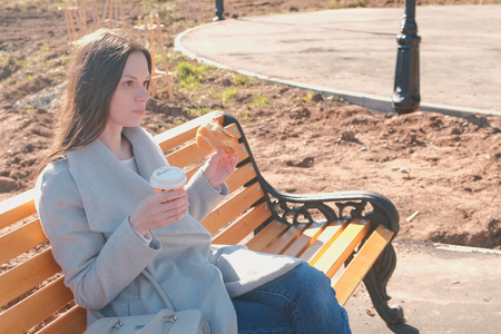Young brunette woman in coat sits on bench in city park, eats bun with sugar and drinks coffee. Springtime. Banco de Imagens