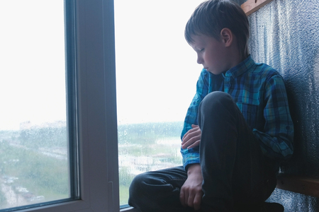 Boy looks out the window sitting in windowsill in the rain and is sad.